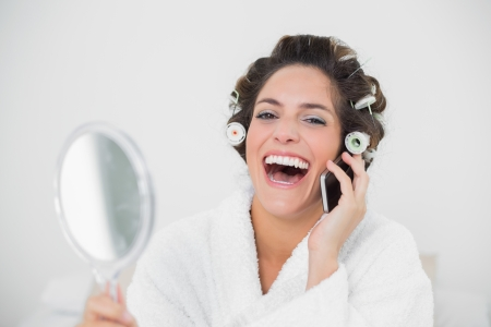 Laughing natural brunette using phone in bedroom photo