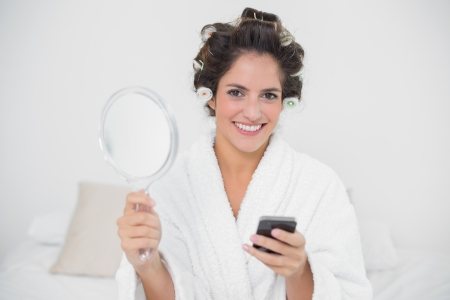 Content natural brunette holding mirror and smartphone in bedroom photo