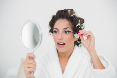 Content natural brunette applying mascara in bedroom photo