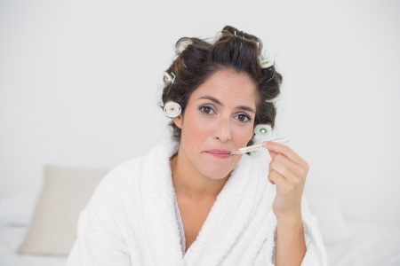 Unhappy natural brunette using thermometer in bedroom photo