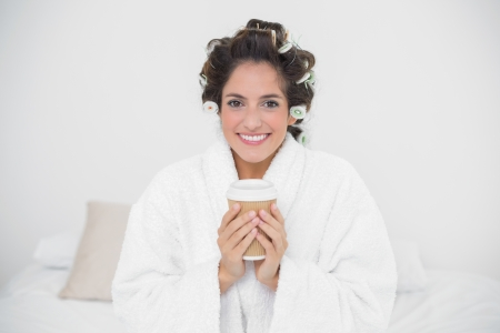 Happy natural brunette holding disposable cup in bedroom photo