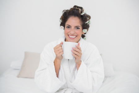 Cheerful natural brunette holding a mug in bedroom photo