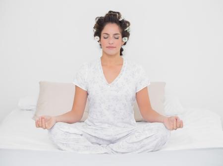 Peaceful natural brunette sitting in lotus pose in bedroom photo