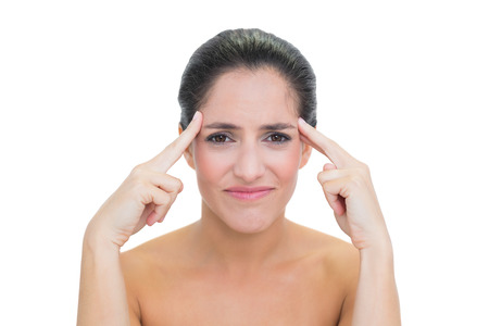 Wincing bare brunette touching her temples on white  Stock Photo