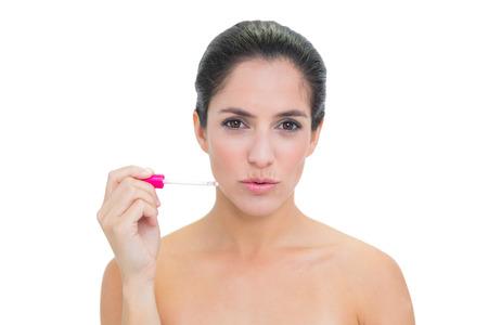 Stern  brunette holding lip gloss on white  photo