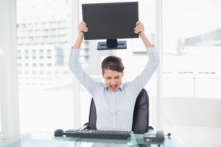 Angry classy brown haired businesswoman throwing her computer screen in bright office photo