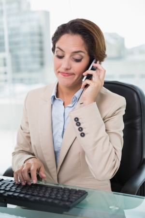 Frowning businesswoman phoning in bright office