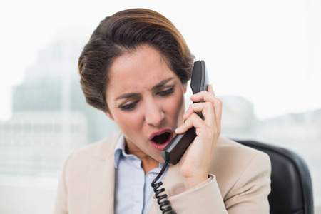 outraged: Outraged businesswoman shouting into phone in bright office Stock Photo