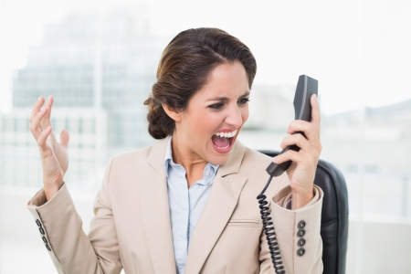 outraged: Outraged businesswoman shouting at phone in bright office Stock Photo