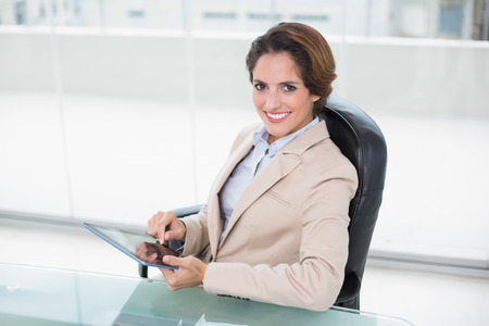classy woman: Cheerful businesswoman holding tablet in bright office Stock Photo