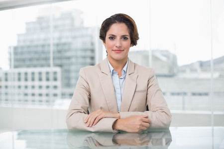 Relaxed businesswoman looking at camera at her desk in bright office photo