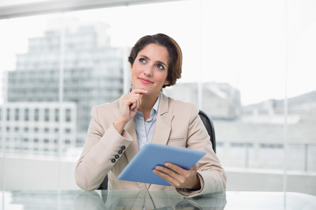 Thoughtful businesswoman smiling and using her digital tablet in bright office photo