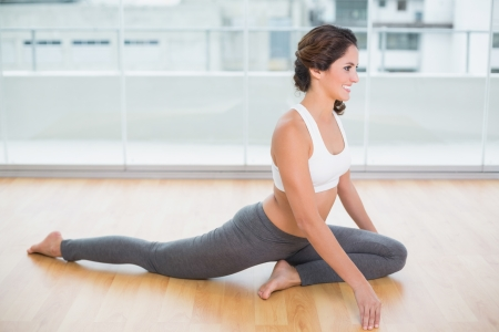 gleeful: Sporty gleeful brunette stretching on the floor in bright room