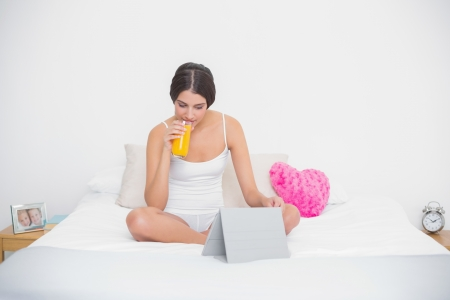 Peaceful young brown haired model in white pajamas drinking orange juice in bright bedroom photo