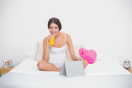 Calm young brown haired model in white pajamas holding a glass of orange juice in bright bedroom photo