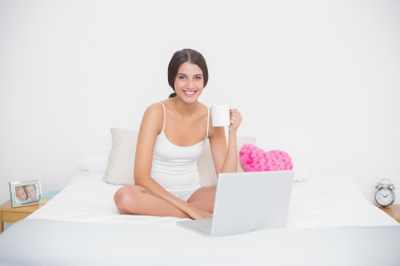 Cheerful young brown haired model in white pajamas drinking coffee while using laptop in bright bedroom photo