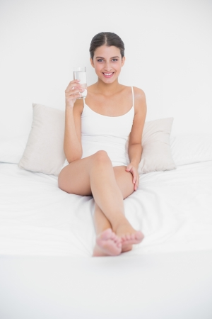 Calm young brown haired model in white pajamas holding a glass of water in bright bedroom photo