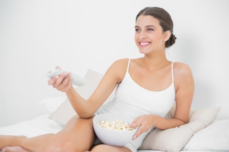 Attractive young brown haired model in white pajamas eating popcorn while watching tv in bright bedroom photo