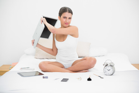 Furious young brown haired model in white pajamas throwing her laptop in bright bedroom photo