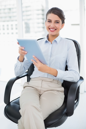 Happy classy brown haired businesswoman holding a tablet pc in bright office photo