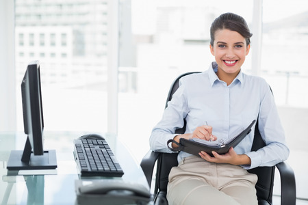 Pleased classy brown haired businesswoman checking her agenda in bright office photo