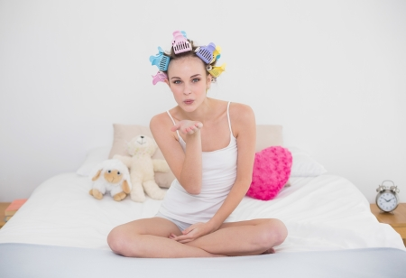 Seductive natural brown haired woman in hair curlers blowing a kiss to the camera in bright bedroom photo