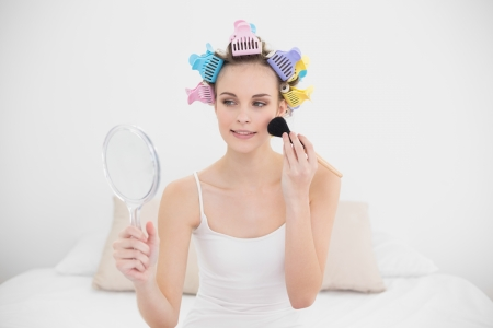 hair curlers: Relaxed natural brown haired woman in hair curlers applying powder on her face in bright bedroom Stock Photo