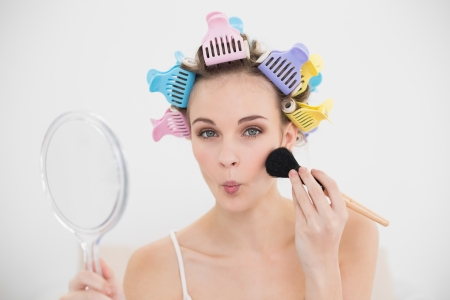 Funny natural brown haired woman in hair curlers applying powder on her face in bright bedroom photo