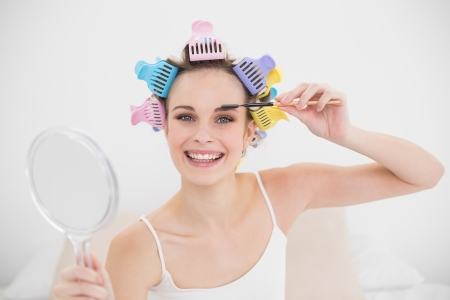 Happy natural brown haired woman in hair curlers brushing her eyebrows in bright bedroom photo
