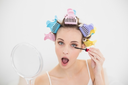 Concentrated natural brown haired woman in hair curlers opening her mouth while applying mascara in bright bedroom photo