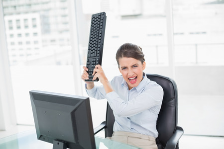 Annoyed classy brown haired businesswoman throwing her keyboard on her computer in bright office photo