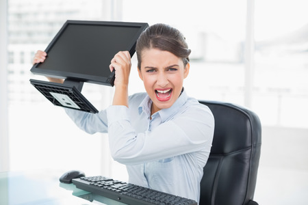 brown haired: Annoyed classy brown haired businesswoman throwing her computer screen in bright office Stock Photo