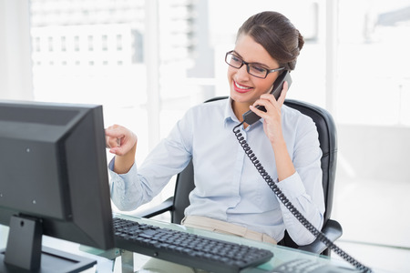 Amused classy brown haired businesswoman answering the telephone in bright office