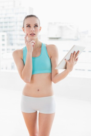 Sporty thoughtful woman using a tablet in bright room photo