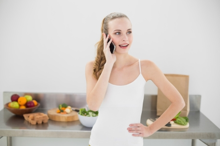 Pretty content woman phoning in bright kitchen photo