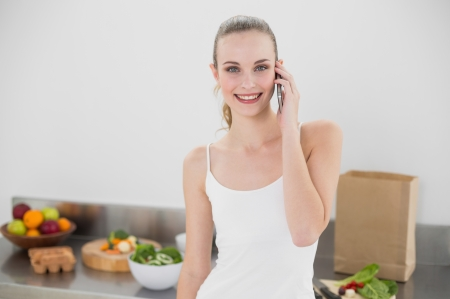 Pretty blonde on the phone in her kitchen photo