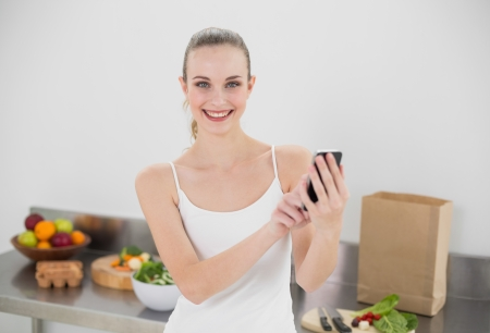 Happy young woman sending a texting in the kitchen at home photo