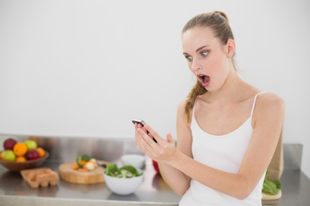 Shocked young woman reading a texting in the kitchen at home photo