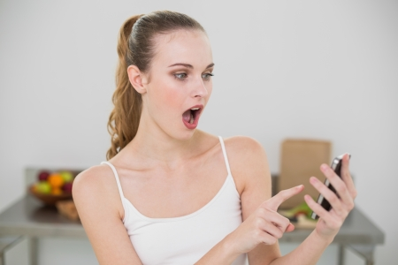 Shocked young woman holding smartphone  in the kitchen at home photo