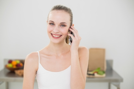 Happy young woman talking on smartphone smiling at camera in the kitchen at home photo