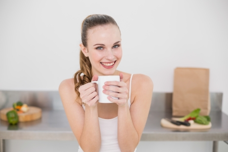 Smiling young woman holding mug in the kitchen at home photo