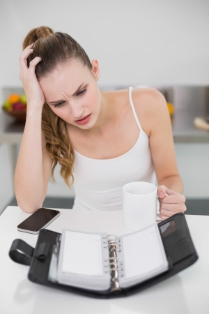 Stressed young woman holding a mug looking at open diary in the kitchen at home photo