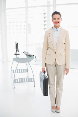 Pleased smart brown haired businesswoman carrying a briefcase in bright office photo