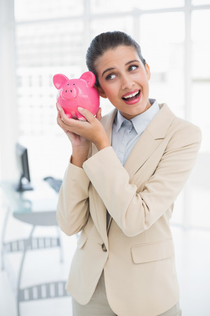 Surprised smart brown haired businesswoman shaking a piggy bank in bright office photo