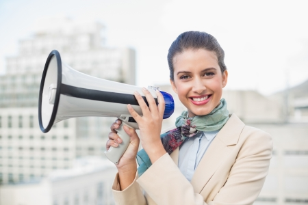 Happy smart brown haired businesswoman holding a megaphone outdoors photo