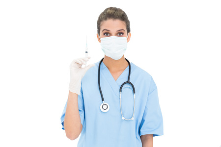 Surprised brown haired nurse in blue scrubs wearing protection mask and holding a syringe on white  photo