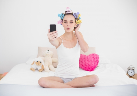 hair curlers: Pouting natural brown haired woman in hair curlers taking a picture of herself with mobile phone in bright bedroom Stock Photo