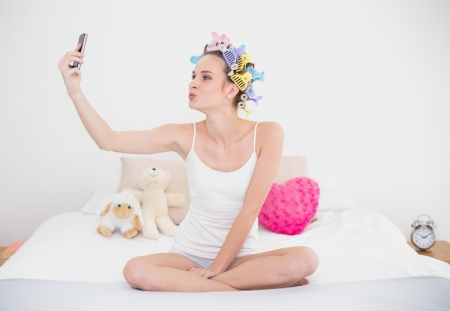Playful natural brown haired woman in hair curlers taking a picture of herself with mobile phone in bright bedroom Stock Photo