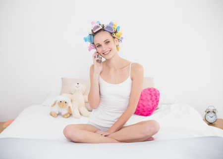 Delighted natural brown haired woman in hair curlers making a phone call in bright bedroom photo