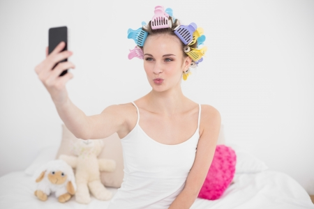 hair curlers: Funny natural brown haired woman in hair curlers taking a picture of herself with mobile phone in bright bedroom Stock Photo